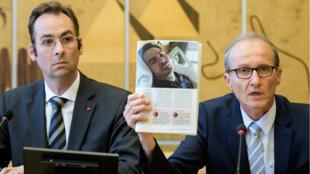 Le neurologue et conseiller des parents de Vincent Lambert, Xavier Ducrocq (à droite), montre une photo de Vincent Lambert en état végétatif depuis 2008. À ses côtés, le directeur du Centre européen pour la justice, Gregor Puppinck. À Genève, le 1er juillet 2019.