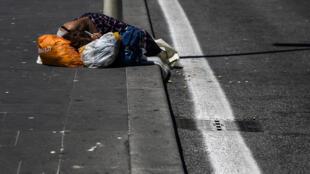 صورة من الارشيف لمشردة تنام على الرصيف قرب محطة ترميني في روما في 4 ايار/مايو 2020