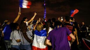 Des supporters célèbrent le titre de l'équipe de France, le 15 juillet 2018 à Paris.