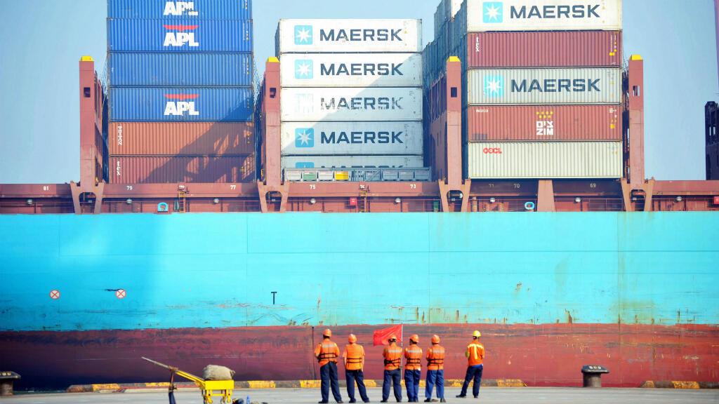 Trabajadores chinos miran cuando un barco se carga en un puerto en Qingdao, provincia de Shandong, este de China, el 13 de julio de 2017.