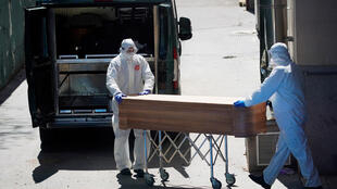 Mortuary workers push a coffin of a person who died at a nursing home during the coronavirus disease outbreak in Leganes, near Madrid, Spain, April 2, 2020.