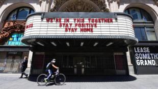 شاب يقود دراجة أمام صالة للسينما في لوس أنجليس كاليفورنيا في 4 أيار/مايو 2020