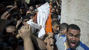 Des Palestiniens transportent le corps de l'un des trois commandants du Hamas tués, le 21 août 2014.