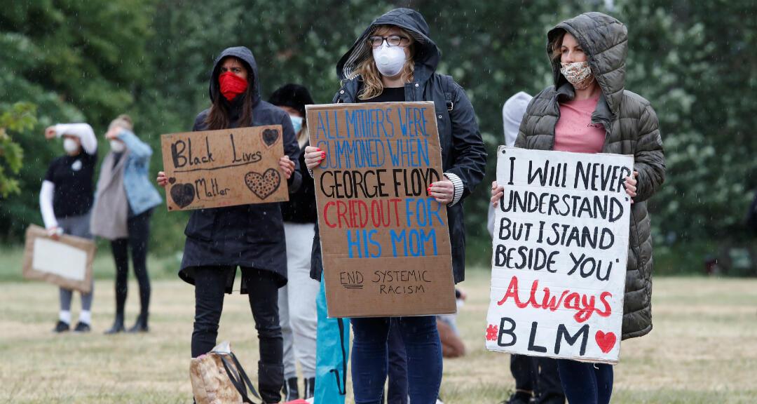 Mujeres con tapabocas por la pandemia de coronavirus se manifiestan en St Albans, Reino Unido en contra del racismo sistemático, el 6 de junio de 2020.