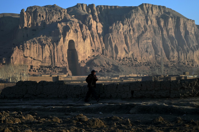 Un homme passe le 5 mars 2021 devant le site de Bamiyan en Afghanistan où deux Bouddhas géants sculptés dans la falaise ont été dynamités par les Taliban en mars 2001