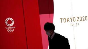 رجل يمر أمام شعار طوكيو 2020 مرتديا كمامة للوقاية من فيروس كورونا