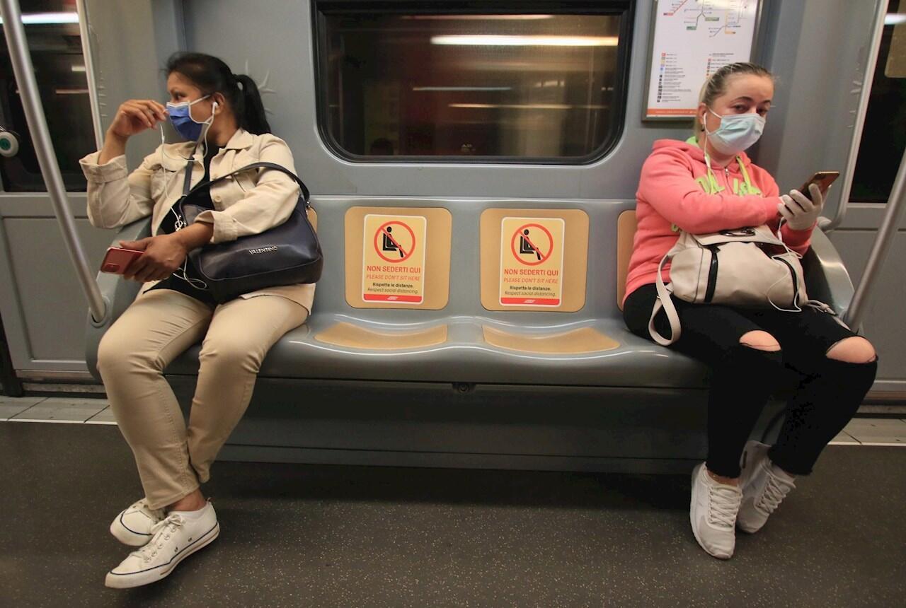 La señalización dentro de un vagón de tren de la compañía municipal de transporte público de Milán (ATM) indica las posiciones preasignadas de pasajeros para mantener el distanciamiento social, una de las medidas para aliviar las restricciones de la crisis de la emergencia del coronavirus, en Milán, norte de Italia, 27 de abril de 2020.
