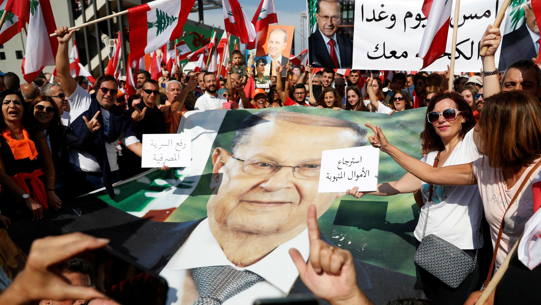 Los partidarios del presidente Michel Aoun sostienen su cartel, durante una manifestación en Baabda, cerca de Beirut, Líbano, el 3 de noviembre de 2019.