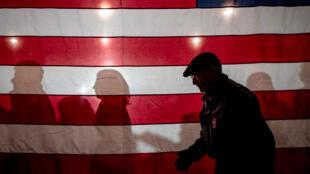 Personas junto a una bandera estadounidense cuando llegan a un evento de campaña del exalcalde de South Bend, Indiana, Pete Buttigieg, para ser el candidato presidencial demócrata 2020, en el Clinton Masonic Center en Clinton, Iowa, EE. UU., el 31 de enero de 2020.