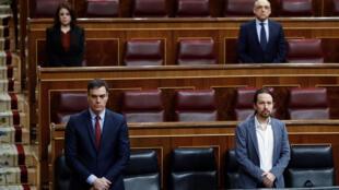 El presidente Pedro Sánchez (izq) y el vicepresidente Pablo Iglesias guardan un minuto de silencio en el banco azul del Gobierno al inicio de un pleno en el Parlamento español sobre la crisis del coronavirus, el 9 de abril de 2020 en Madrid
