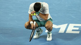Novak Djokovic grimaces after a point against Milos Raonic on Sunday night