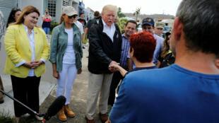 El presidente estadounidense Donald Trump y la primera dama Melania Trump  saludan a la gente durante una caminata por un barrio afectado en San Juan, el 3 de octubre de 2017.