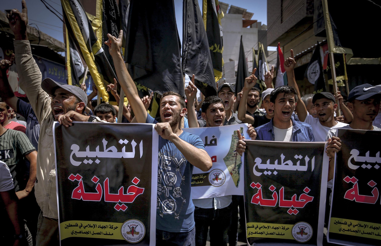 """متظاهرون فلسطينيون يرفعون لافتات كتب عليها """"التطبيع خيانة"""" خلال تظاهرة في غزة بتاريخ 14 أغسطس/آب 2020."""