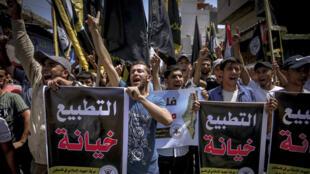 """متظاهرون فلسطينيون يرفعون لافتات كتب عليها """"التطبيع خيانة"""" خلال تظاهرة في غزة بتاريخ 14 آب/اغسطس 2020"""
