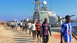 مهاجرون غير شرعيين في قاعدة عسكرية بحرية في طرابلس بعد إنقاذهم من قبل خفر السواحل الليبي في 29 آب/أغسطس 2017
