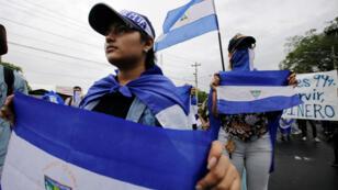 Estudiantes sostienen banderas nacionales durante una protesta contra el presidente de Nicaragua, Daniel Ortega, el 2 de agosto de 2018.