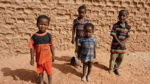 A group of children pose for photographs on a street in Agadez, northern Niger on April 1, 2017