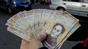 En décembre 2016, devant la banque centrale, à Caracas, un homme change ses bolivars avant qu'ils ne perdent davantage de valeur.
