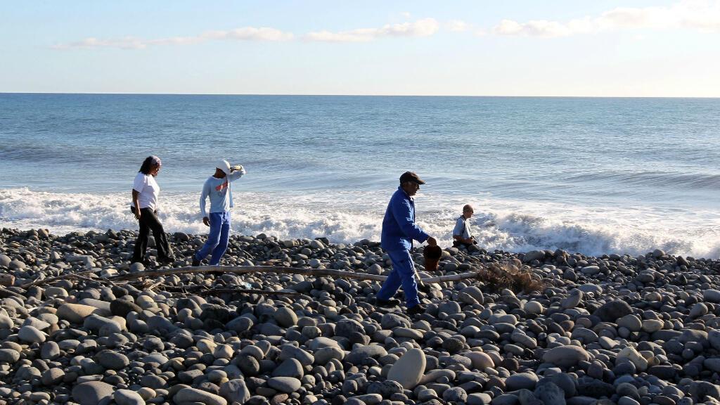 Des volontaires recherchent d'autres débris sur la plage de Saint-André à La Réunion, le 31 juillet 2015.