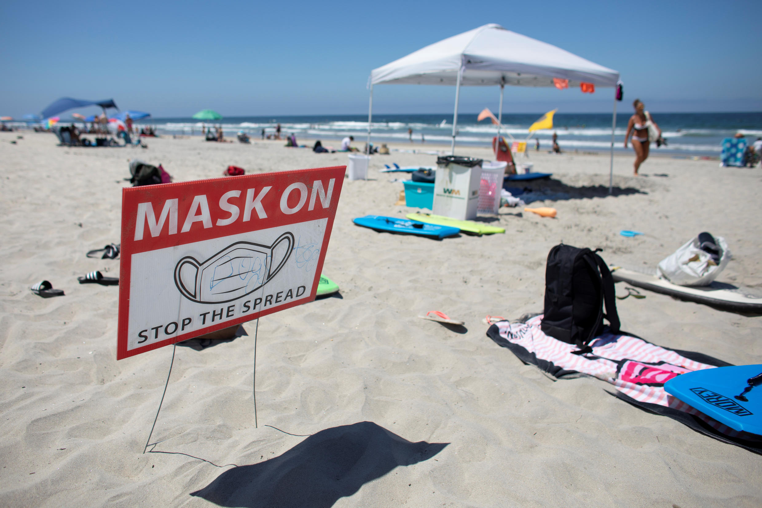 A sign requiring the use of masks is seen at the beach as California reported its largest number of new coronavirus infections in a single day, during the outbreak of the coronavirus disease (COVID-19) in Del Mar, California, U.S., July 15, 2020.