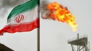 Una llamarada de gas en una plataforma de producción de petróleo en los campos petrolíferos de Soroush se ve junto a una bandera iraní. El lunes 5 de noviembre, EE. UU. volverá a imponer sanciones a Irán, pero permitirá que ocho países sigan importando petróleo.