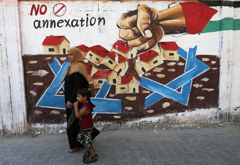 فلسطينية تسير أمام حائط رسم عليه رسومات تعبر عن رفض الفلسطينيين لضم إسرائيل أراض من الضفة الغربية في رفح، قطاع غزة، 14 يوليو/ تموز 2020.
