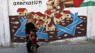 Une femme palestinienne passe devant un graffiti dénonçant l'annexion de la Cisjordanie, à Rafah, dans la bande de Gaza, le 14 juillet 2020.