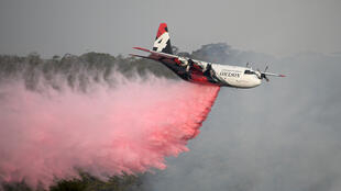 The NSW Rural Fire Service Large Air Tanker (LAT) drops fire retardant on the Morton Fire burning in bushland close to homes in Penrose in the NSW Southern Highlands, south of Sydney, Australia on January 10, 2020.