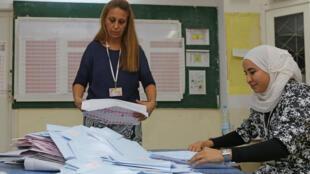 Des membres du personnel de l'instance chargée des élections(Isie) en Tunisie trient des bulletins de vote dans la capitale, Tunis, le 6octobre2019, lors des législatives.