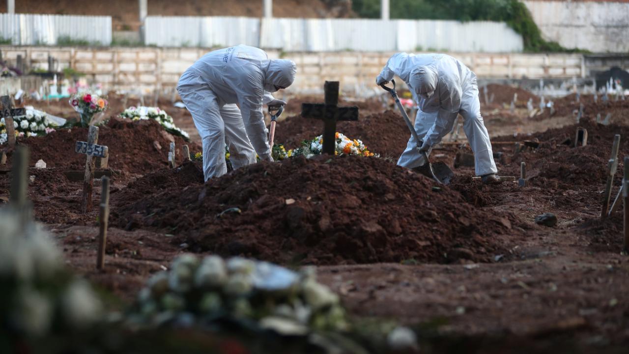 Imagen de un cementerio de Río de Janeiro, donde operarios, totalmente protegidos, entierran a una víctima del coronavirus, el 9 de mayo de 2020.