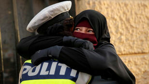 Una mujer de 37 años que lleva puesto un nikab, llora cuando un oficial de policía la abraza durante una manifestación contra la prohibición del uso de esa prenda, en Copenhague, Dinamarca, el 1 de agosto de 2018.