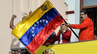 El presidente de Venezuela, Nicolás Maduro, sostiene una bandera venezolana mientras habla desde un balcón en el Palacio Presidencial de Miraflores a una multitud de simpatizantes para anunciar que estaba rompiendo relaciones diplomáticas con los Estados Unidos, en Caracas, el 23 de enero de 2019.