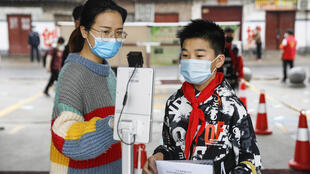 Una mujer ayuda a un estudiante a comprobar su temperatura corporal con escáner término en una escuela de primaria de la ciudad de Pingdingshan City, provincia de Henan, el 8 de mayo de 2020 en el centro de China