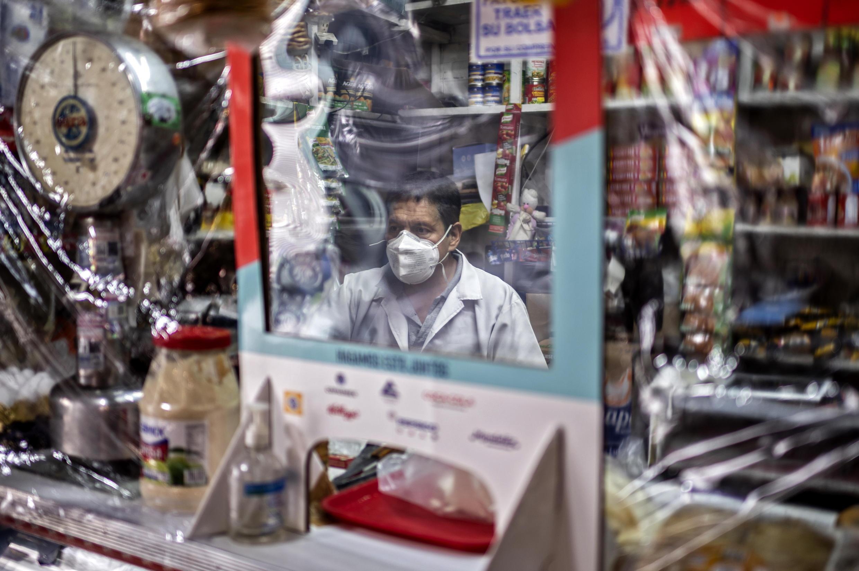 Un comerciante atiende a un cliente detrás un plástico para protegerse del coronavirus en el mercado de Iztapalapa, en Ciudad de México el 22 de junio de 2020.