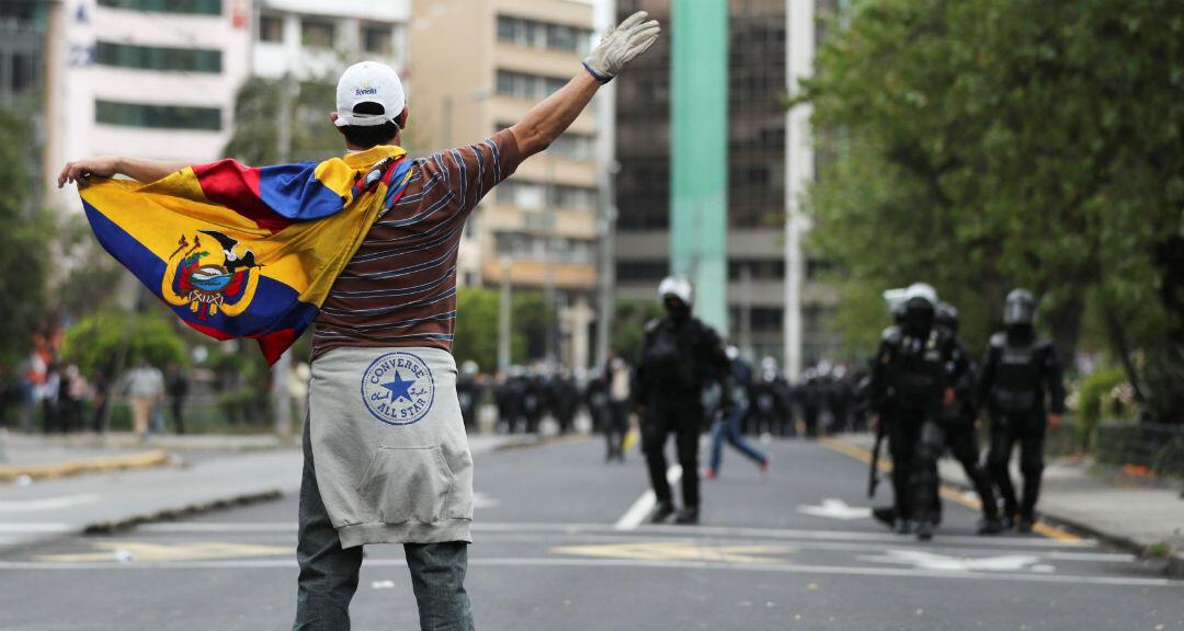 Un manifestante se planta delante de la Policía en las manifestaciones de Ecuador mientras lleva una bandera.4 de octubre de 2019. Quito, Ecuador.