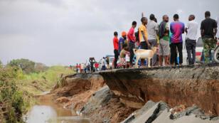 Des habitants se tiennent près d'un tronçon de route endommagé entre Beira et Chimoio, dans le district de Nhamatanda, dans le centre du Mozambique, le 19mars2019, cinq jours après le passage du cyclone Idai.