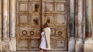 مصل يقف أمام أبواب كنيسة القيامة في البلدة القديمة في القدس الشرقية المحتلة، والمغلقة بسبب تفشي فيروس كورونا المستجد في 4 نيسان/أبريل 2020
