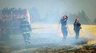 رجال إطفاء في أحد الحقول التي اجتاحتها الحرائق في لورين شمال فرنسا