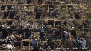 Workers dig graves in Santiago's General Cemetery after health authorities ordered them to prepare for a possible surge in deaths from COVID-19