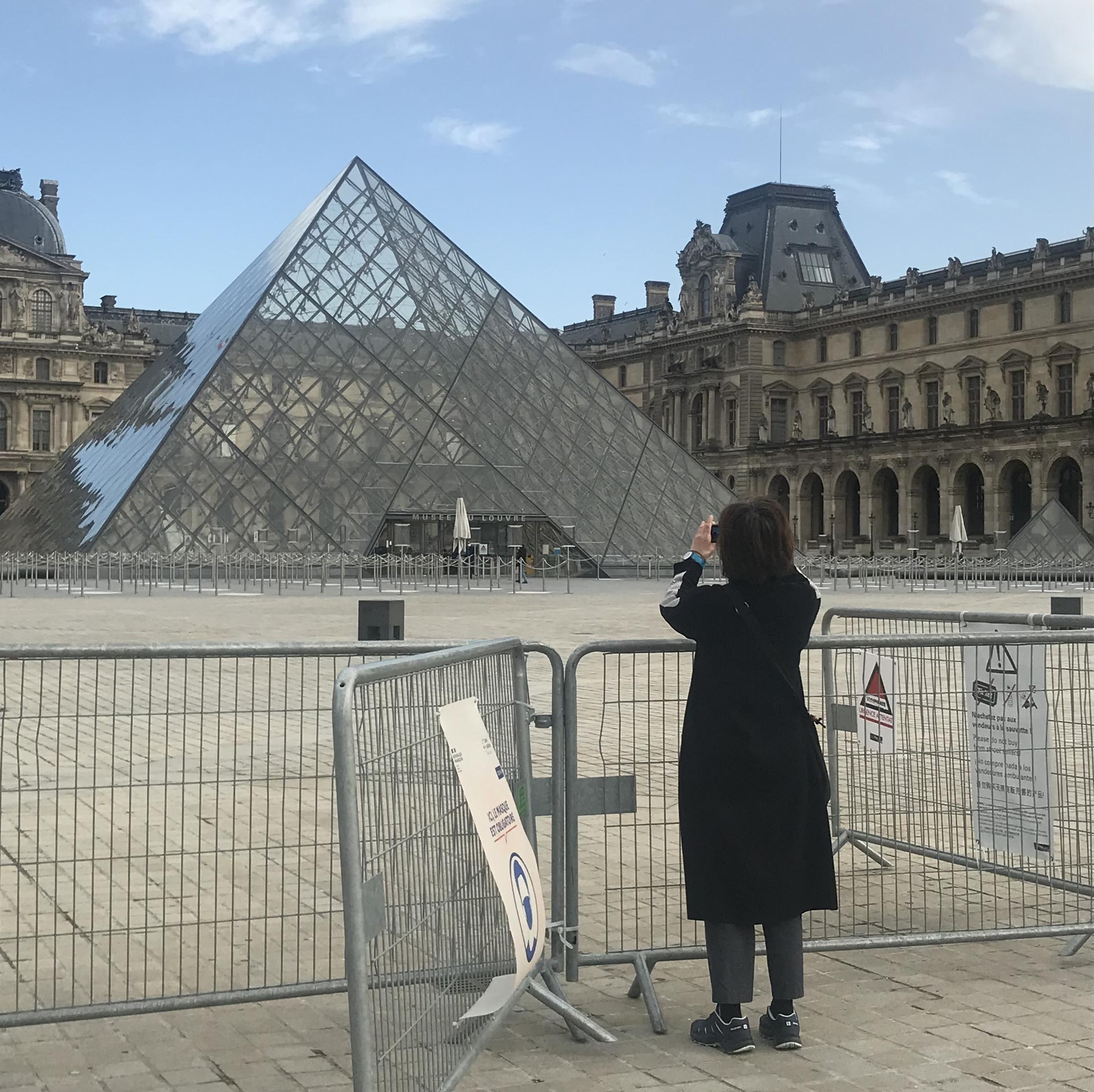 A woman takes a photo in front of the closed gates of the Louvre museum in Paris. On February 22, 2021