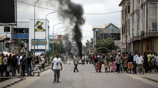 John Wessels, AFP   People look on as protesters burn tyres during a demonstration calling for the President of the Democratic Republic of the Congo (DRC)t o step down on January 21, 2018, in Kinshasa.