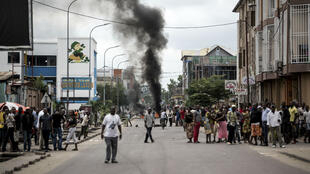 John Wessels, AFP | People look on as protesters burn tyres during a demonstration calling for the President of the Democratic Republic of the Congo (DRC)t o step down on January 21, 2018, in Kinshasa.