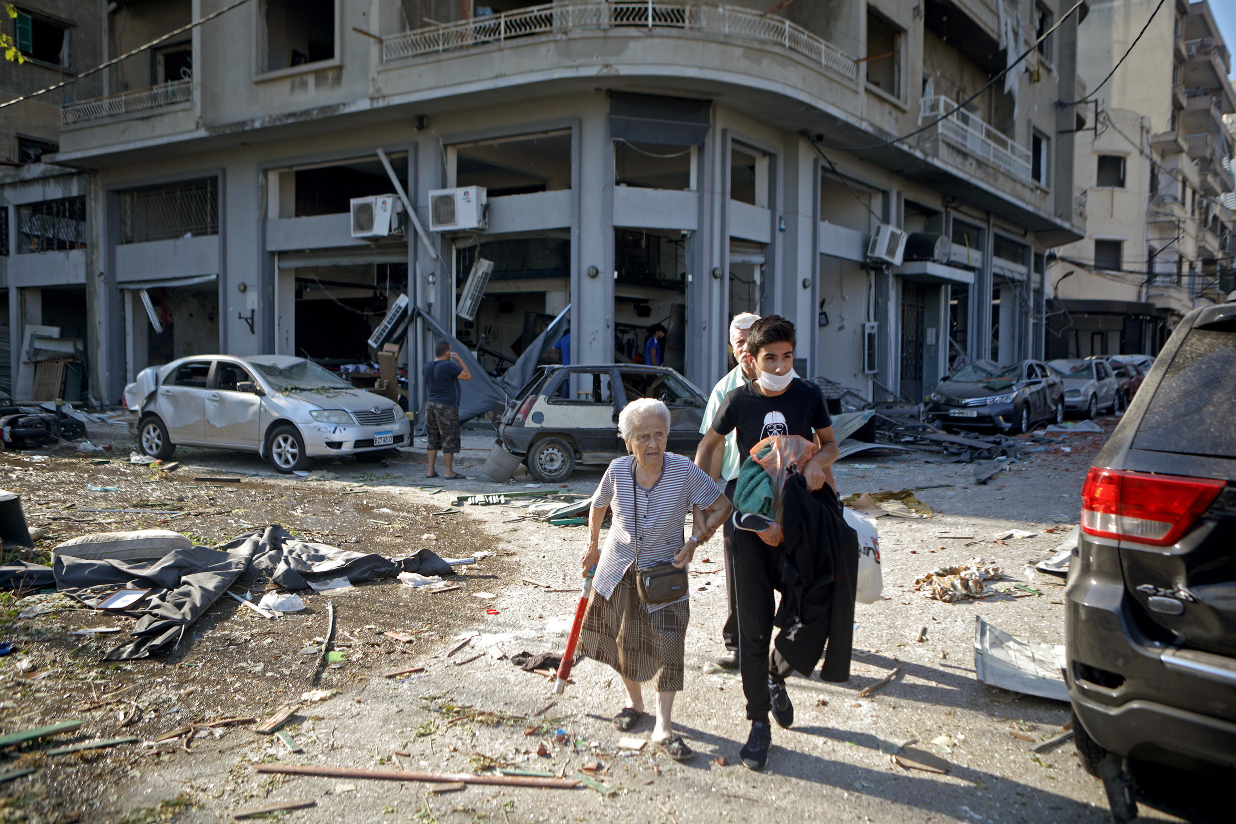 A woman is evacuated from a district of Beirut partially destroyed by the double explosion on August 5, 2020.