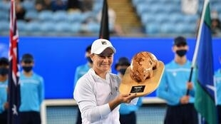 World number one Ashleigh Barty celebrates with the trophy after beating Garbine Muguruza to win the the Yarra Valley Classic on Sunday