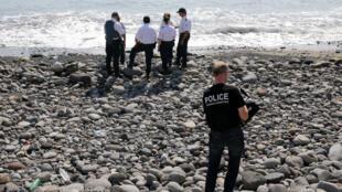 Des policiers inspectent, dimanche 2 août, des débris métalliques retrouvés sur une plage de La Réunion.