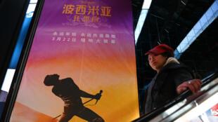 Una mujer baja por unas escaleras eléctricas y pasa frente a un cartel de la película 'Bohemian Rhapsody' en un cine en Beijing, China, el 27 de marzo de 2019.