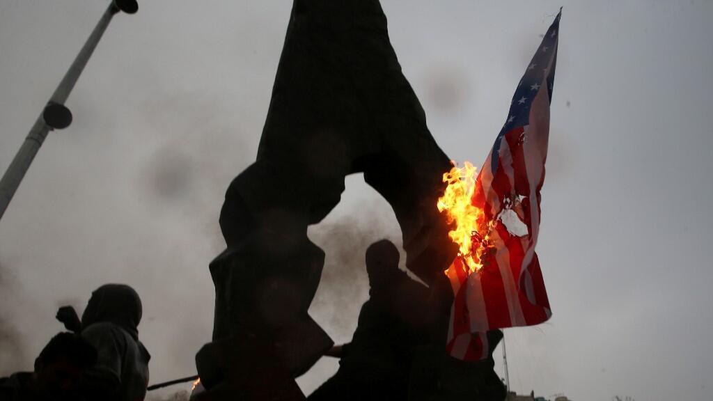 Los iraníes queman banderas estadounidenses e israelíes mientras se reúnen para llorar al general Qassem Soleimani, jefe de la élite de la Fuerza Quds, que murió en un ataque aéreo en el aeropuerto de Bagdad, en Teherán, Irán, el 3 de enero de 2020.