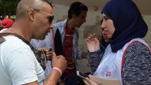 عاملون في الهيئة التونسية العليا المستقلة للانتخابات يجولون شوارع العاصمة لإقناع الناخبين بتسجيل أسمائهم للتصويت في للانتخابات العامة