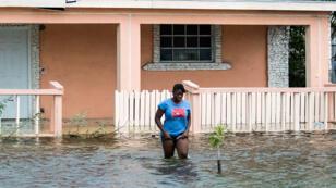 Une femme marche dans une rue inondée après le passage de l'ouragan Dorian sur les Bahamas, à Nassau le 2 septembre 2019.