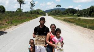 Familia venezolana del estado Aragua posa para una foto mientras intentan hacer autostop hacia la ciudad de Boa Vista, luego de obtener el estatus de refugiado o residencia temporal, a través de la Policía Federal y el Alto Comisionado de las Naciones Unidas para los Refugiados (ACNUR), en el control fronterizo de Pacaraima, estado de Roraima, Brasil. 10 de agosto de 2018.